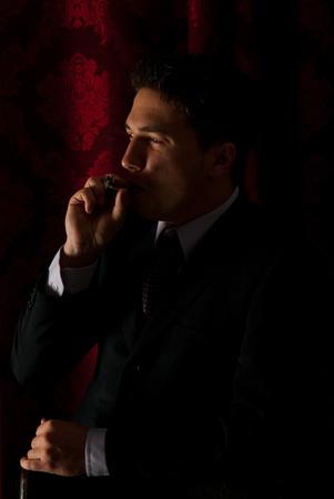 hombre fumando puro: Perfil del hábito de fumar hombre elegante en la noche y mirando a la luz Foto de archivo