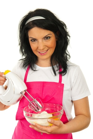 Smiling woman holding bixer and bowl with flour and eggs isolated onw hite background photo