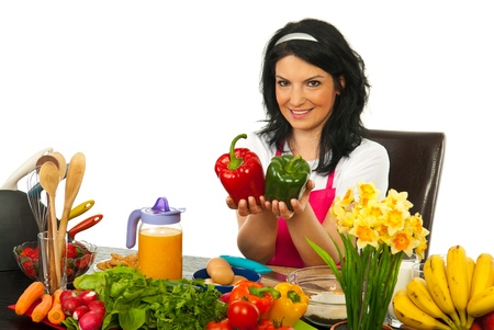Happy woman sitting on chair in kitchen and showing colorful big peppers against white background photo