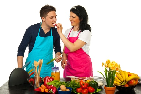 ing: Happy couple in kitchen,woman giv ing man to eat vegetables