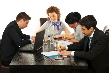 four person: Busy business people in office sitting on chairs at meeting table and writing on papres Stock Photo