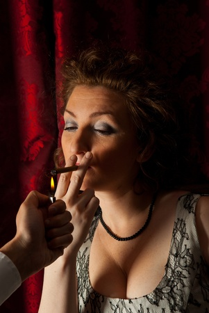 Hand man offers to a womans cigarette lighter fire to light her  cigarette in darkness photo