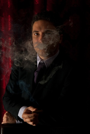 Elegant man standing in cigar smoke in darkness Stock Photo - 13367341