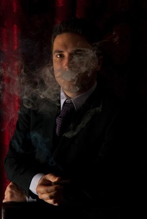 cigar smoke: Elegant man standing in cigar smoke in darkness