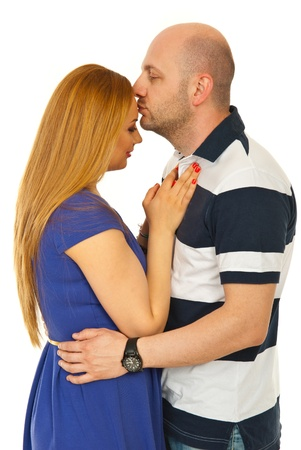 Man kissing forehead woman and standing in embrace isolated on background photo
