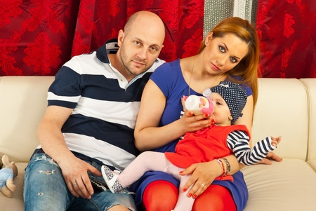 Family with baby sitting on their couch in living room photo