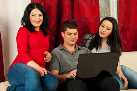 threesome: Happy friends sitting on couch home and using laptop Stock Photo