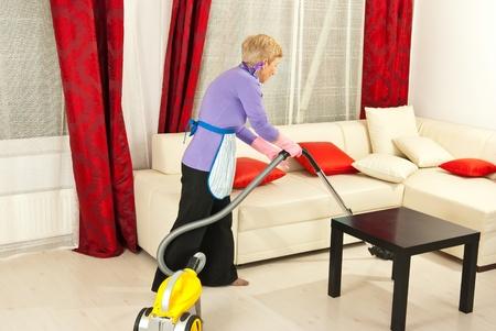 Senior donna pulizie a casa con aspirapolvere Archivio Fotografico