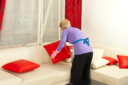 Back of senior woman arrange pillows on sofa home Stock Photo