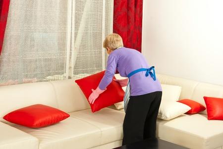 Back of senior woman arrange pillows on sofa home Foto de archivo