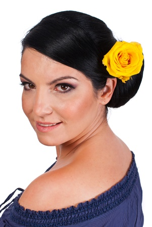 Beautiful smiling woman with spanish bun hairstlye and yellow rose in hair looking over shoulder isolated on white background photo