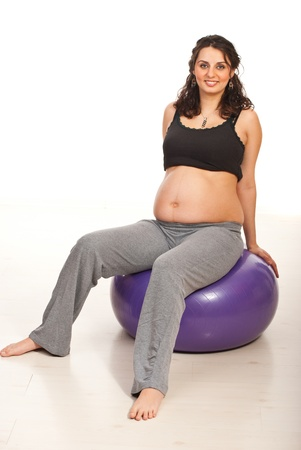 Happy pregnant woman sitting on fitness  against white background Stock Photo - 15043235