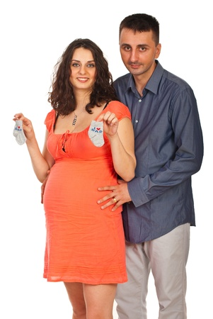 whie: Happy future parents standing n embrace and mother holding socks isolated on whie backgrond