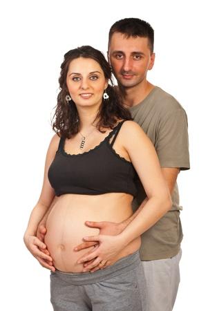 cocaina: Felice coppia incinta in piedi ine mbrace ed entrambe le mani che tengono sulla pancia isolato su sfondo bianco