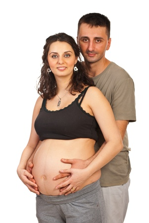 cocaine: Happy pregnant couple standing ine mbrace and both holding hands on tummy isolated on white background