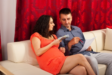 Future parents calculate their expenses and sitting together on  couch photo