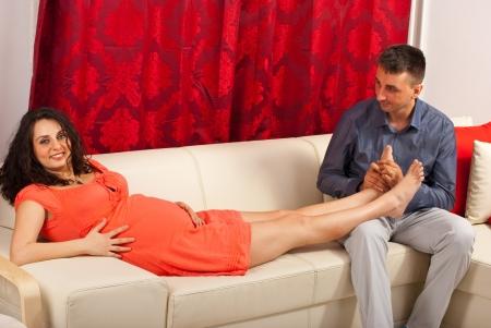 Marito massaggiare le gambe moglie in stato di gravidanza e seduti insieme sul divano a casa loro