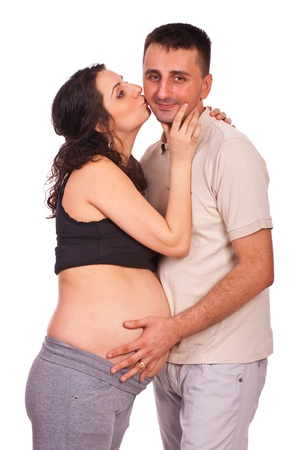 Happy pregnant woman kissing her husband and standing in embrace isolated on white background photo
