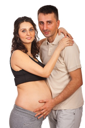 Pregnant couple standing in embrace isolated on white background photo