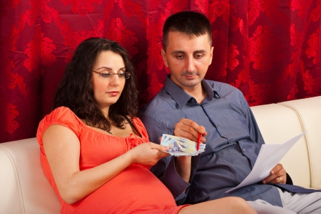 Future parents sitting on couch in their living room and counting their money  photo