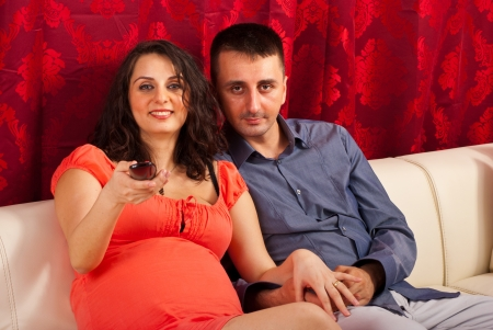 Happy future parents watching tv in their living room photo