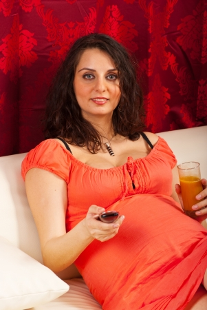 Pregnant woman watching tv and drinking orange juice in living room photo