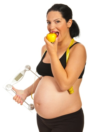 Healthy pregnant woman holding scales and eating apple isolated on white background photo
