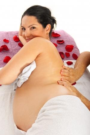 masaje corporal: Hombre terapeuta de masaje espalda a la mujer embarazada en la mesa contra el fondo blanco