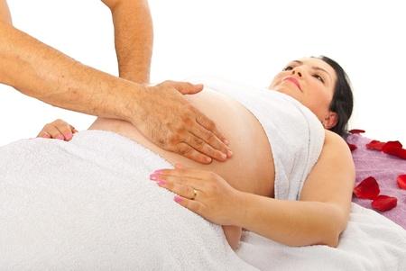 mujeres embarazadas: Terapeuta haciendo masaje a la mujer embarazada vientre contra el fondo blanco