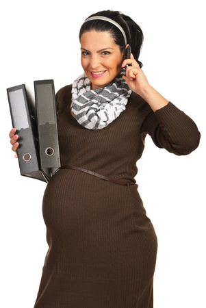 Happy business pregnant woman talking by phone mobile and holding folders isolated on white background photo