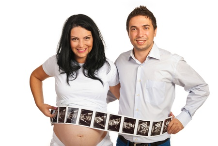Couple holding long  number of ultrasound images in front of their bellys isolated on white background photo