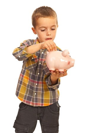 shot put: Little boy put a coin into piggy bank isolated on white background Stock Photo