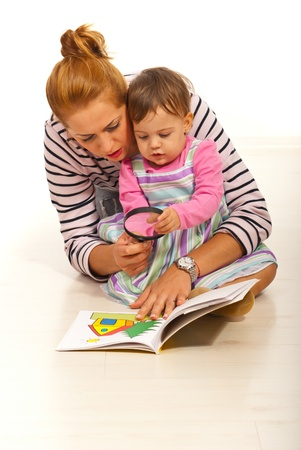 Mother with girl reading book  home and  holding magnifier  photo