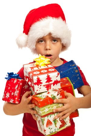 Amazed boy with Santa hat having arms full of Christmas gifts isolated on white background Stock Photo - 16120151