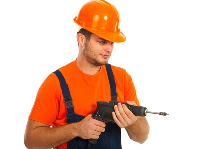 driller: Young worker man in uniform holding a drill isolated on white background