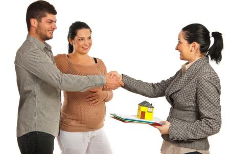 Zwangere vrouw en haar man het kopen van nieuwe huis en schudden hand met makelaar vrouw geïsoleerd op witte achtergrond Stockfoto