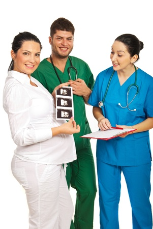 sonograma: Feliz equipo de m�dicos con la mujer embarazada mostrando sonograma del beb� aislado en el fondo blanco