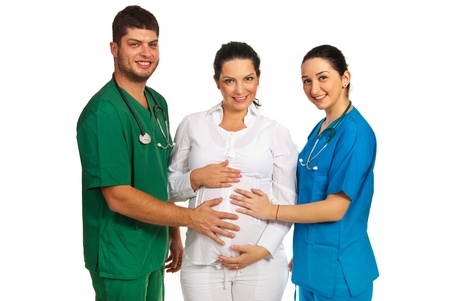 Happy team of doctors holding their hands on pregnant woman belly isolated on white background photo