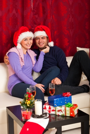 Happy couple with Santa hats sitting on couch home and celebrating Christmas photo