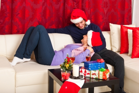 Happy Xmas couple having conversation and sitting together on couch home photo