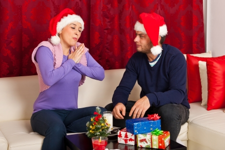 Christmas couple eating good biscuits with milk and having conversation in their home photo