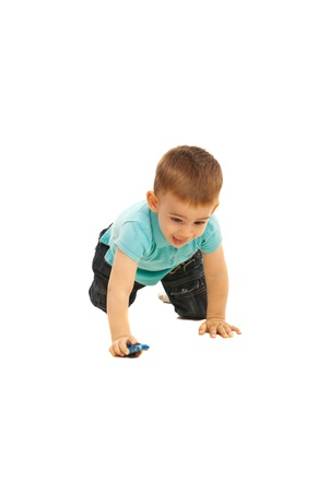 Happy boy crawling and play with small toy car isolated on white background photo