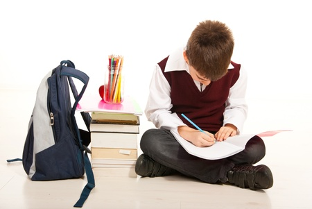 school bags: Schoolboy making homework and sitting with legs crossed on the floor isolated on white background Stock Photo