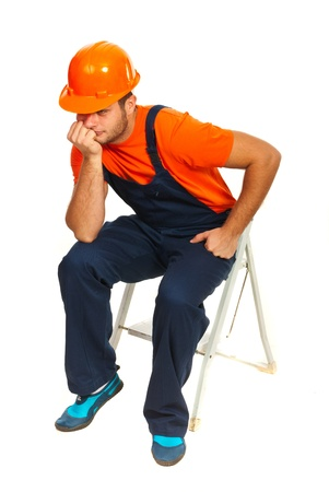 step ladder: Sad constructor worker sitting and waiting on step ladder isolated on white background