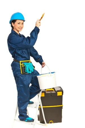 Painting worker woman standing on step ladder isolated on white background photo