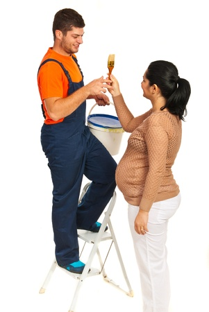 pregnant woman with husband: Pregnant wife giving paint brush to her husband to painting  their room isolated on white background Stock Photo