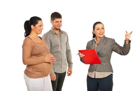 Immobiliare donna agente immobiliare che effettua la presentazione di coppia incinta isolato su sfondo bianco