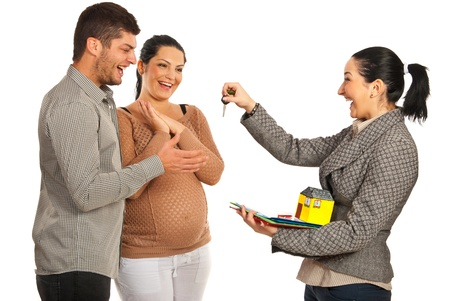 Happy real estate agent woman giving keys to pregnant couple isolated on white background