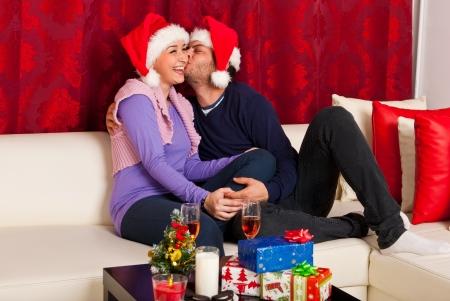 Gelukkige paar lachen en kussen en het vieren Kerstnacht in hun huis