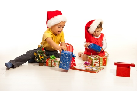Two kids arrange  Christmas gifts and sitting together on floor photo